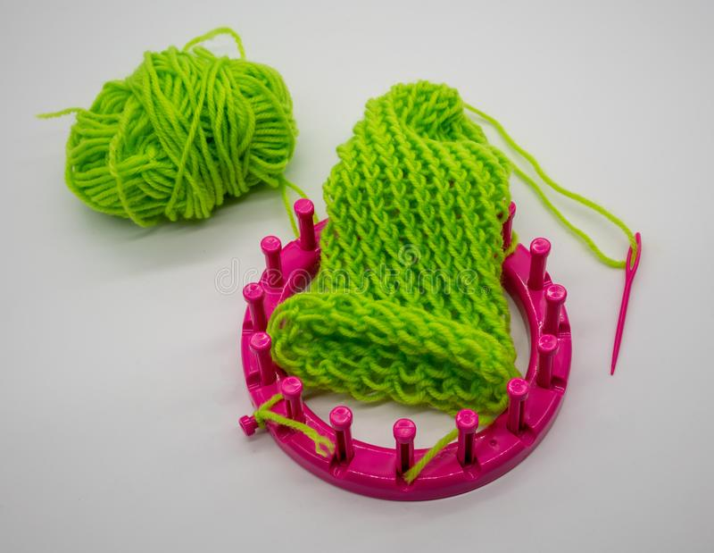Round knitting loom kit and green yarn with basic stitches isolated on white stock photo