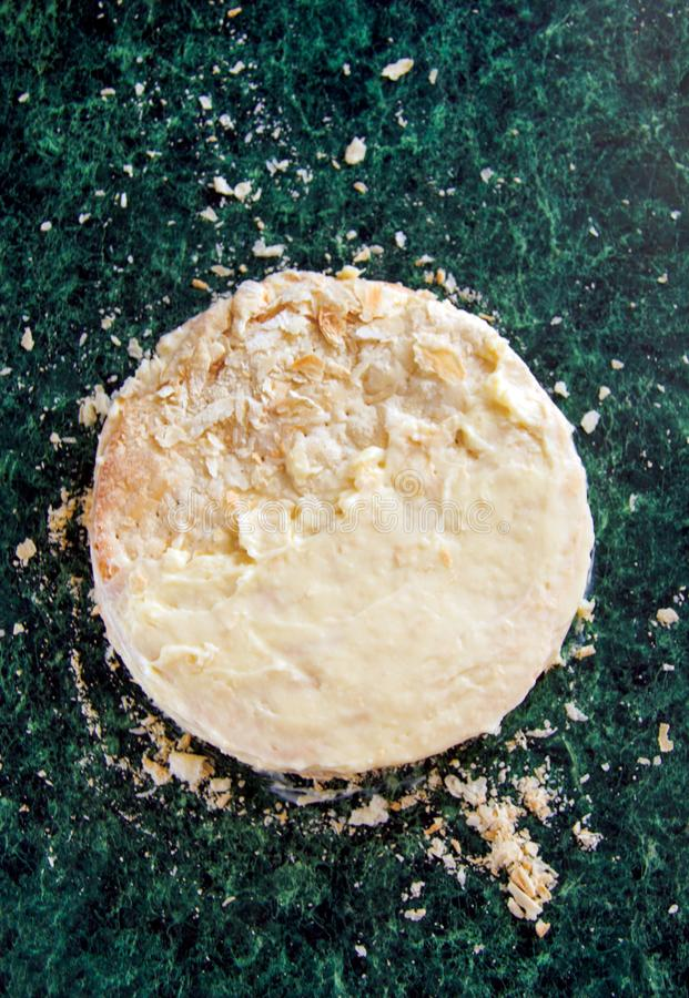 Round layered napoleon cake with custard and sprinkled crumbs on a green marble table, top view. The process of cooking, recipe. Desserts stock photos