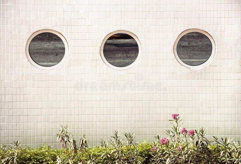 3 round lustrzanego okno na białym kafelkowym budynku z rzędu zdjęcie royalty free