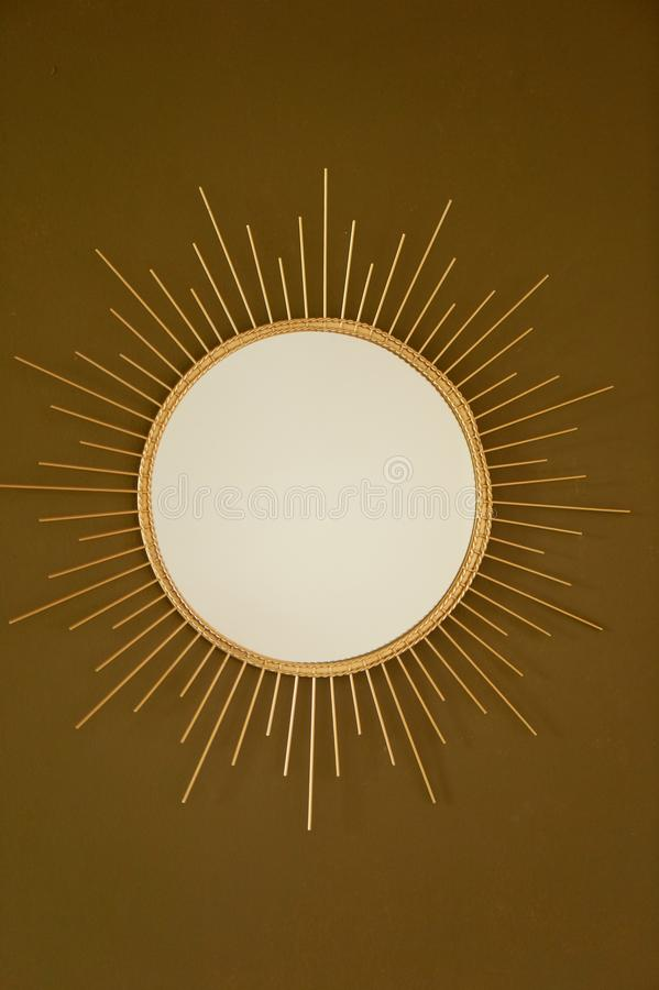 A round mirror on a brown and gold wall. In the form of the sun in a Golden metal frame. Interior design stock photography
