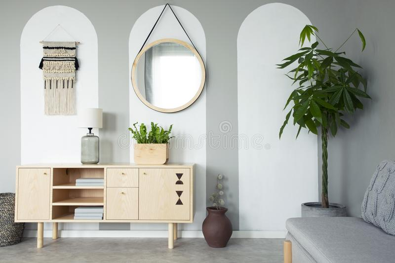 Round mirror hanging on the wall in real photo of grey living room interior with retro cupboard with lamp and books and fresh stock photo