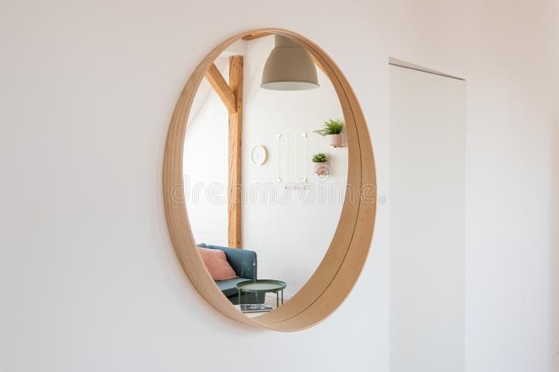 Round mirror on the living room wall. With reflection of living room stock photography