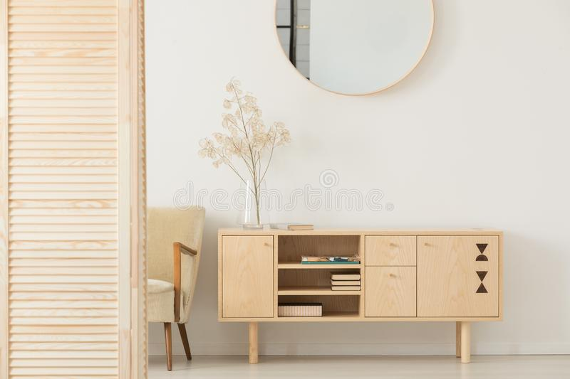 Round mirror on white wall above wooden cabinet in simple anteroom interior with armchair royalty free stock photo