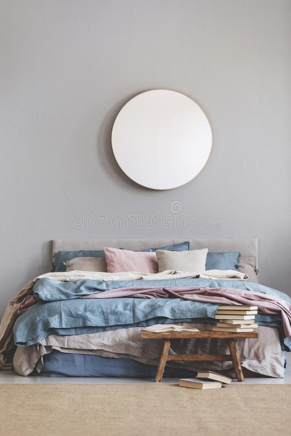 Round mirror in wooden frame on grey wall of elegant bedroom interior with comfortable bed with pastel, blue and pink bedding. Round mirror in wooden frame on stock image