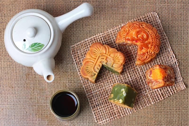 Round mooncake.8 grains and salted eggs and squred mooncake filled red beans, stirred in green tea and chopped macadamia nuts serv royalty free stock images