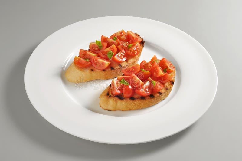 Round naczynie z piec na grillu chlebowym i pomidorowym bruschetta zdjęcie royalty free