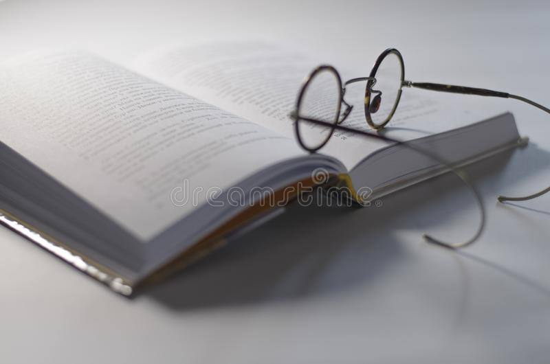 Round the old glasses lay on an open white book, which lies on a white background royalty free stock photography
