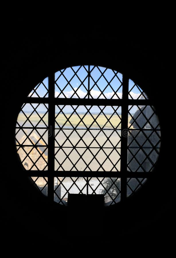 Round old window with a great view of the tide. stock photo