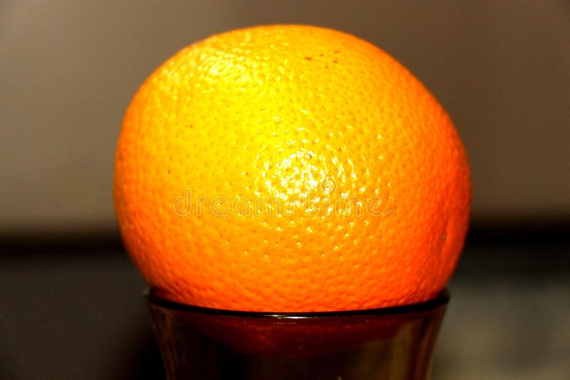 Round one ripe orange on the dishes royalty free stock photography