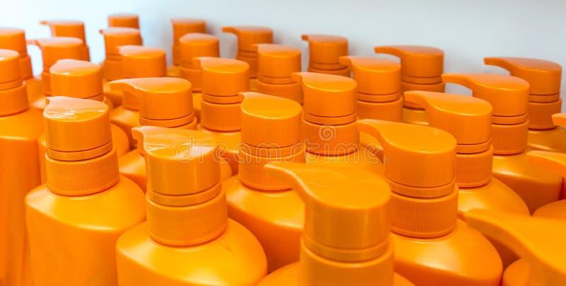 Round orange plastic bottle with dispenser pump for liquid soap, shampoo, shower gel, lotion, body milk stock photo