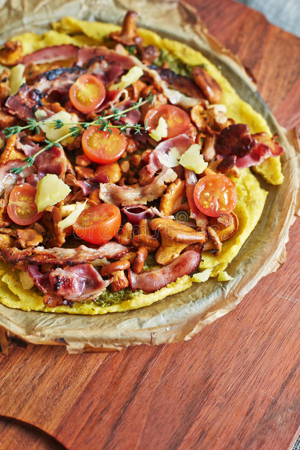 A round pie with cheese, bacon, mushrooms and tomatoes royalty free stock image