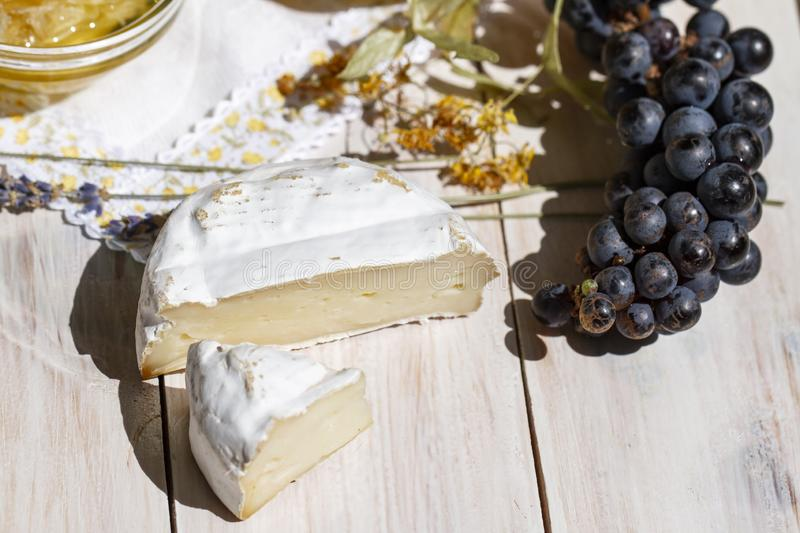 Round piece of brie cheese, black grapes and lavender on a wooden white background, top view. Camembert cheese. Close up stock photography