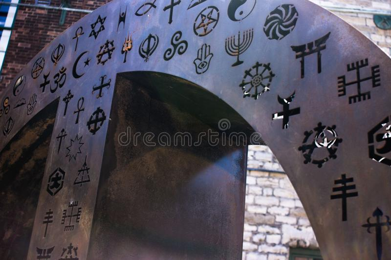 Round piece of metal with religious symbols. Metal peace sign with many religious symbols which sends a big beautiful message royalty free stock photo