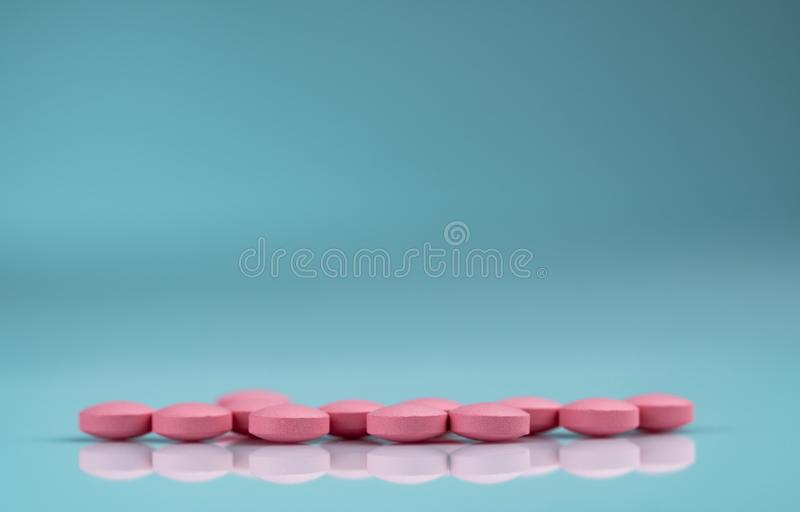 Round pink tablets pill on gradient background. Vitamins and minerals plus folic acid vitamin E and zinc in drug bottle. On gradient background. Pink tablets royalty free stock image
