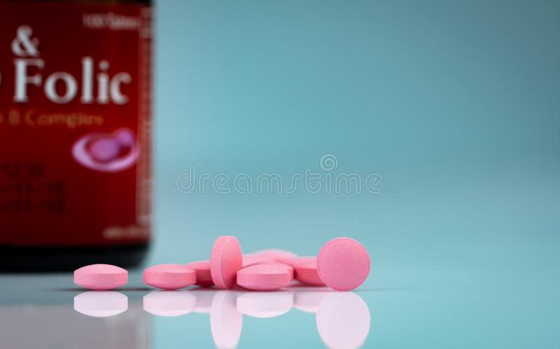 Round pink tablets pill on gradient background. Vitamins and minerals plus folic acid vitamin E and zinc in drug bottle. On gradient background. Pink tablets royalty free stock photography