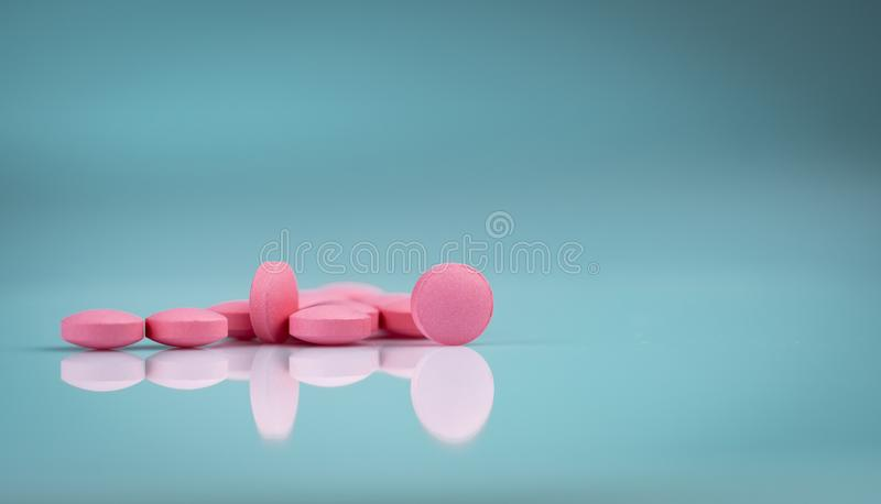 Round pink tablets pill on gradient background. Vitamins and minerals plus folic acid vitamin E and zinc. On gradient background. Pink tablets pills for during royalty free stock photo