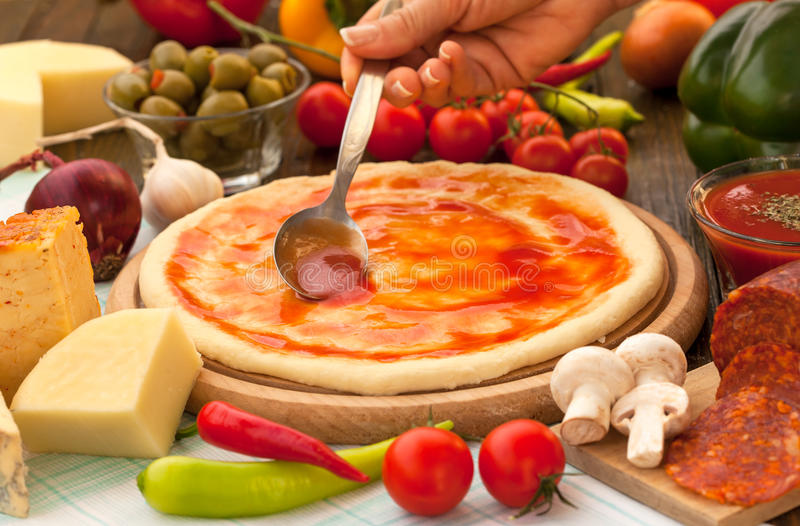 Round pizza dough with tomato sauce. Putting tomato sauce on top of the pizza stock images