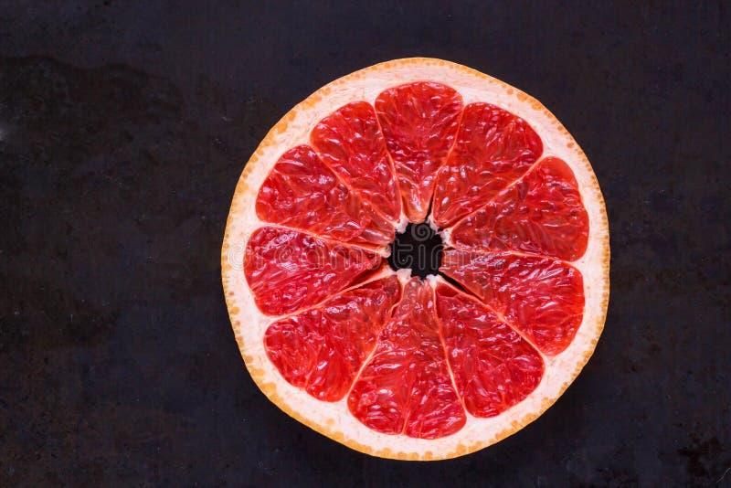 Round plasterek świeży Grapefruitowy na czarnym tle z copyspace zdjęcie stock
