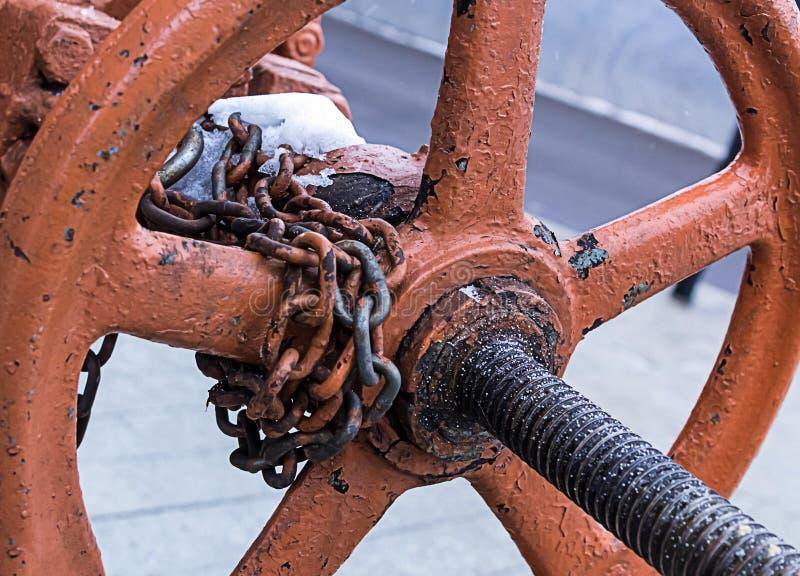 Round pomarańczowej klapy ośniedziała stara część produkci cewienia łańcuchu długi fiksacja w jeden pozyci na zamazanym tle obraz royalty free