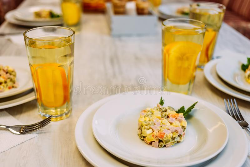 Round portion of winter salad with a sprig of parsley on a white plate on the table. Large transparent glasses with orange juice. Canteen stock image