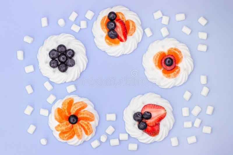 Round rama beza z czarnymi jagodami, truskawkami, marshmallow i tangerines na lawendowym tle, Odg?rny widok obraz stock