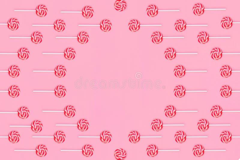 Round rama lizaki z czerwonych i bielu lampasami na różowym tle zdjęcie stock