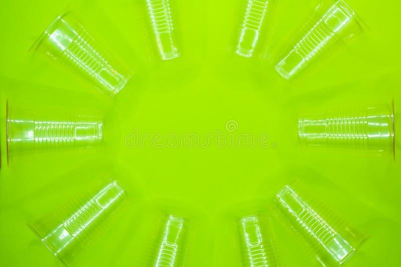 Round rama trasparent plastikowe rozporządzalne filiżanki na zielonym tle Opróżnia przestrzeń w centrum wizerunek zdjęcia royalty free