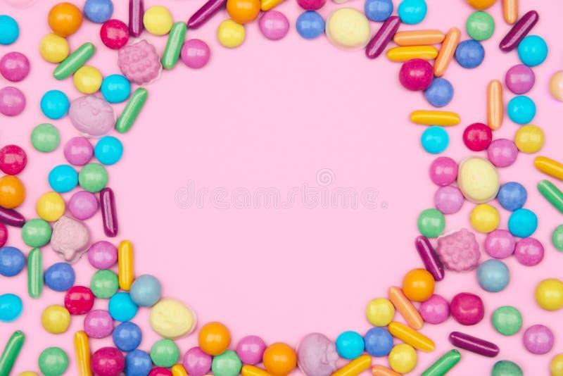 Round rama z asortowanymi barwionymi cukierkami na różowym tle obraz royalty free