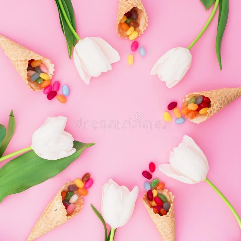 Round rama z jaskrawym cukrowym cukierkiem w gofrów tulipanach i rożkach kwitnie na różowym tle Mieszkanie nieatutowy, odgórny wi obraz stock