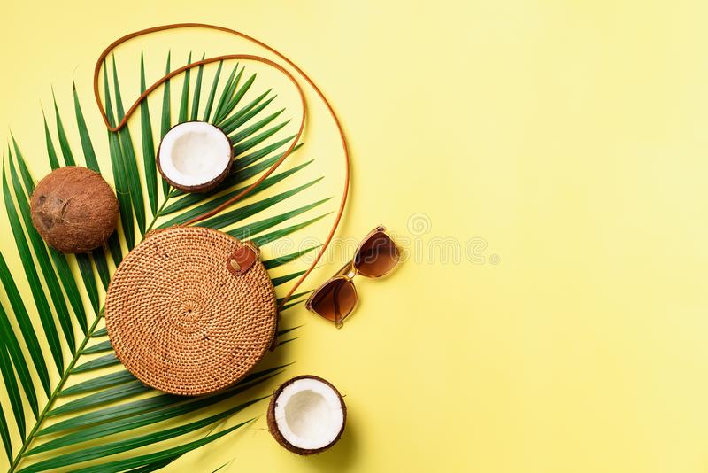 Round rattan bag, coconut, birkenstocks, palm branches, sunglasses on yellow background. Banner. Top view with copy stock images