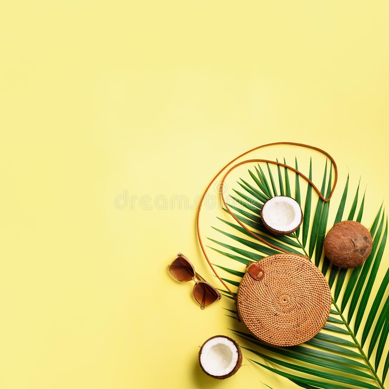 Round rattan bag, coconut, birkenstocks, palm branches, sunglasses on yellow background. Square crop. Top view, copy stock image