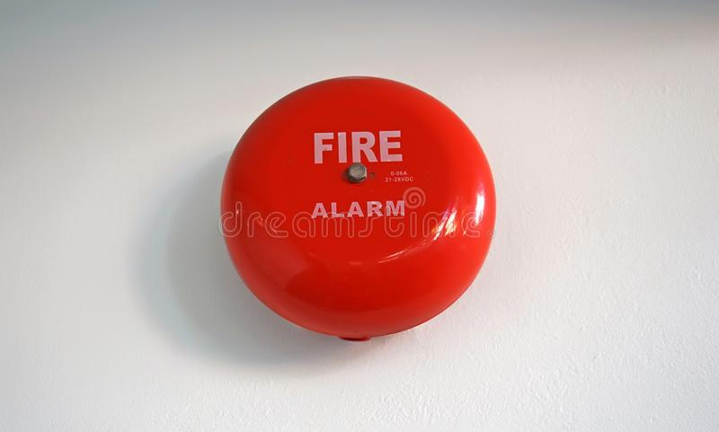 Round red fire alarm mounted on a cement wall royalty free stock image