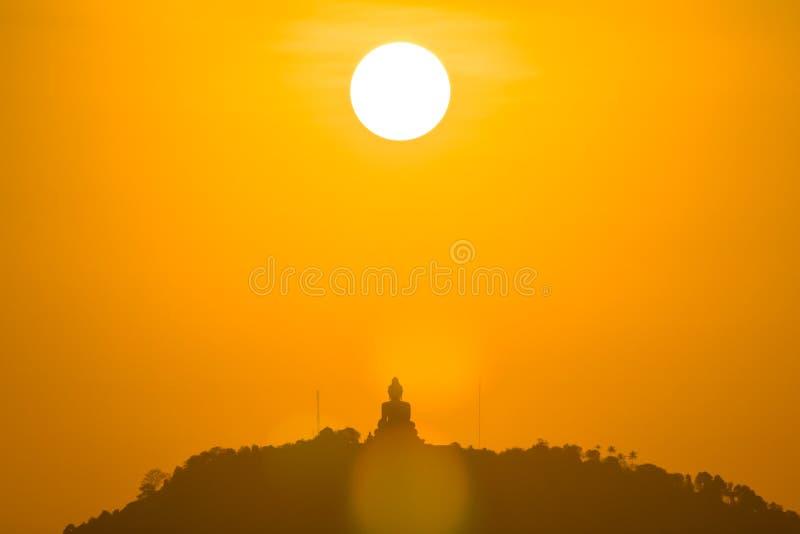 Round red sun above big Buddha royalty free stock photos