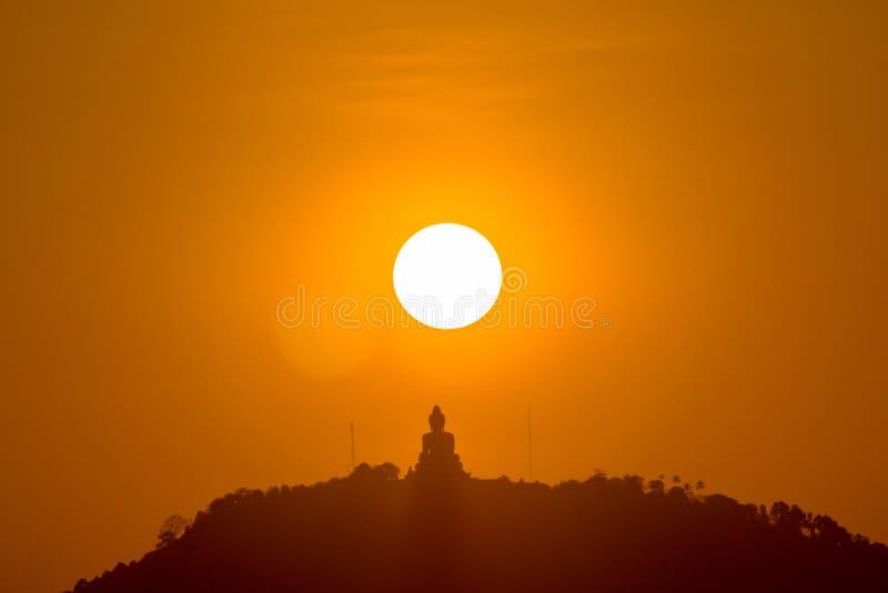 Round red sun above big Buddha stock image