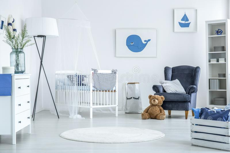 Round rug in white interior. Of cozy kid bedroom with oversize lamp and white crib with veil royalty free stock photo