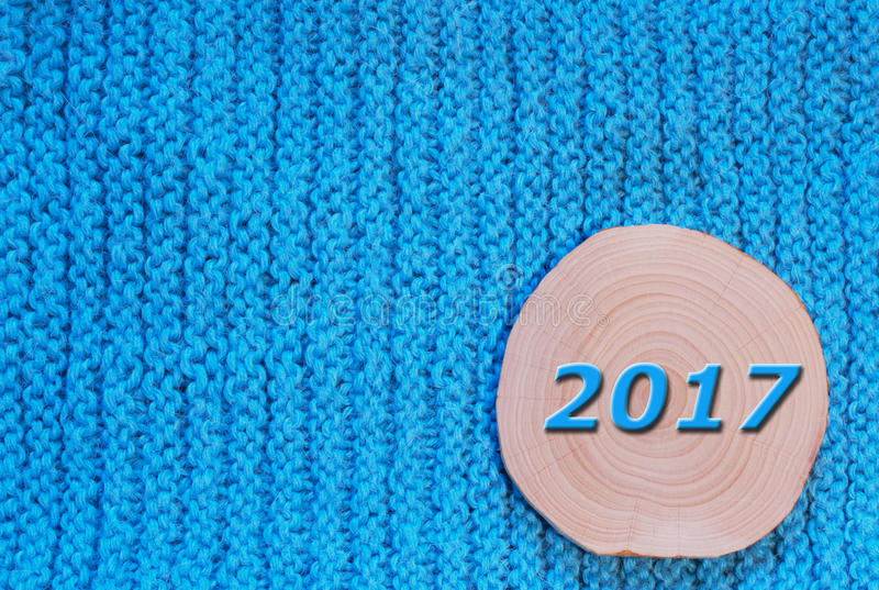 Round saw cut alder and blue date 2017 on blue knitted fabric b. Ackground. New Year`s and Christmas background stock photos