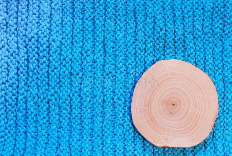 Round saw cut alder on blue knitted fabric background. Round cut alder with annual rings on a background of blue , knitted vertical rows of knitted fabric royalty free stock photos