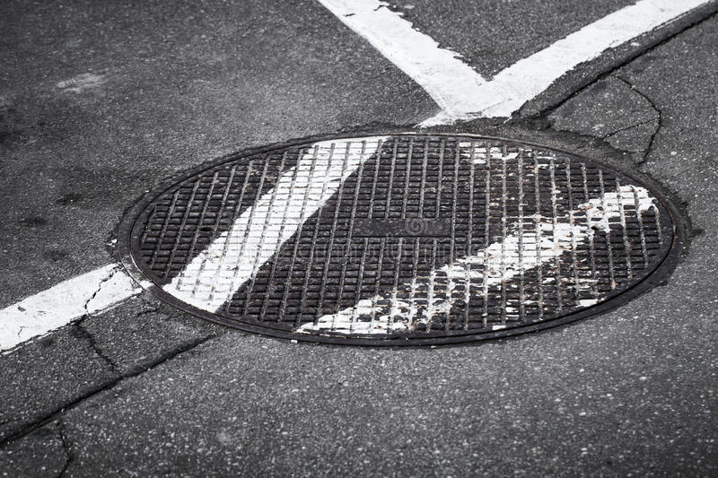Round sewer manhole on asphalt road. With white marking lines royalty free stock images