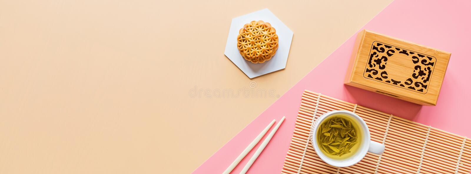 Flat lay of Chinese Festival dessert, Mid Autumn Festival Moon cake on colorful background with green tea and chopsticks. Top view stock images
