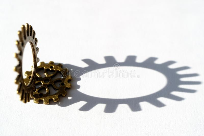Round shaped serrated gear casting shadow on white background royalty free stock photography