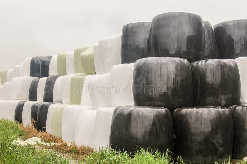 Round silo bales wrapped in a black,white and green membrane and laid like a pyramid. stock photos