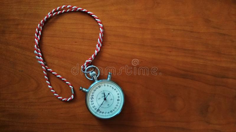 Round Silver-colored Analog Stopwatch on Brown Wooden Panel royalty free stock images