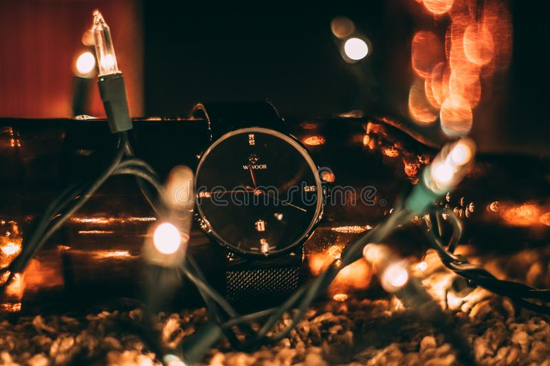 Round Silver-colored Analog Watch With Black Band Surrounded With String Lights Selective Focus Photography stock image