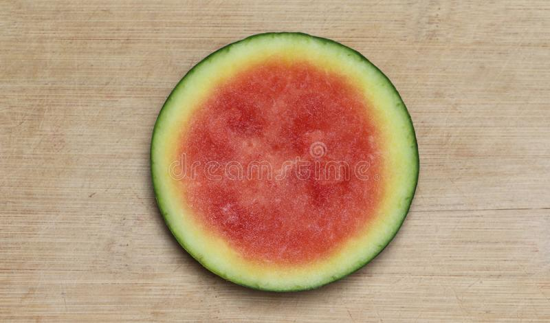 Round slice of pink seedless watermelon with a yellow and green rind, centered on a worn, pale brown cutting board stock images
