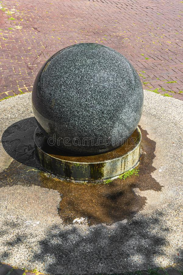 Round smooth granite stone water ball. On a village square stock photos