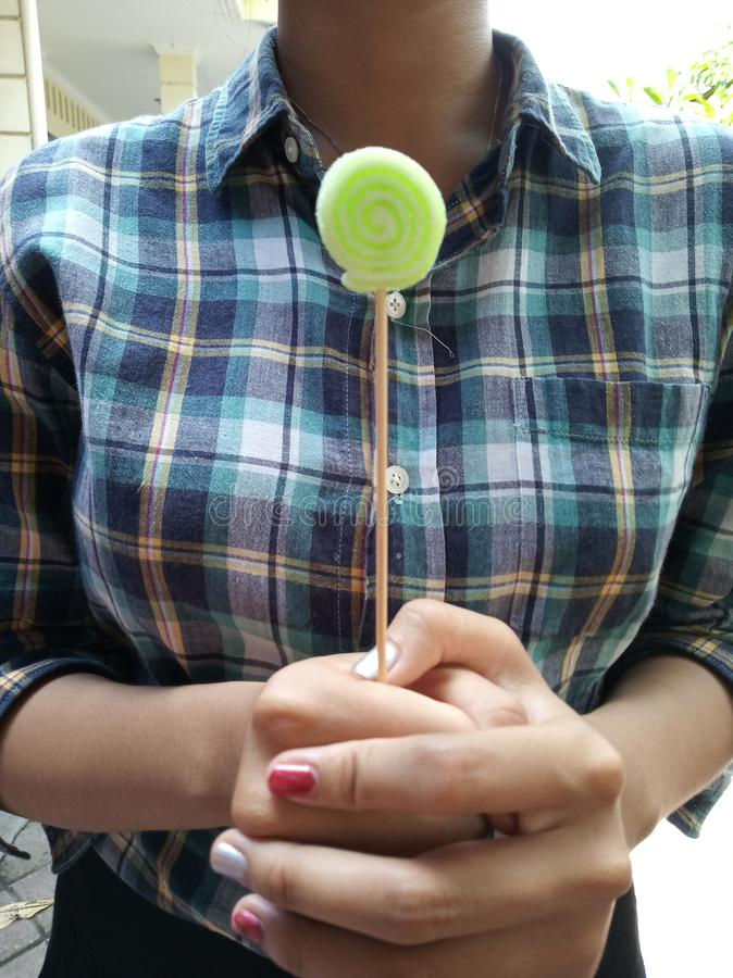 A girl standing holding a green candy stick. royalty free stock photos