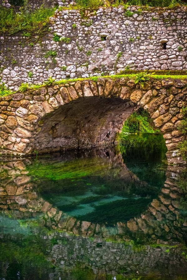 Round stone bridge reflected in river water vertical background royalty free stock photo