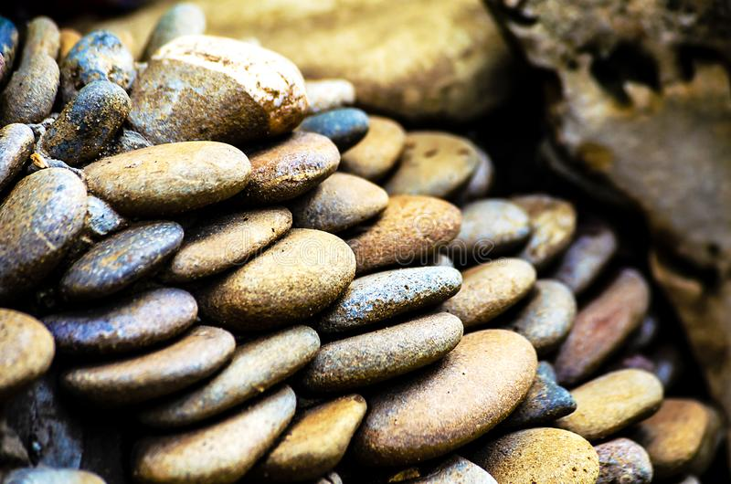 Round stones of pebbles are beautifully arranged in a pile royalty free stock images