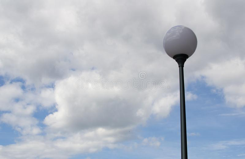 Round street lamp against a cloudy sky royalty free stock photography
