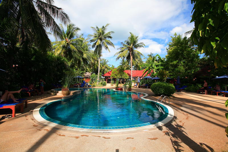 Round swimming pool, sun loungers next to the garden and bungalow stock image